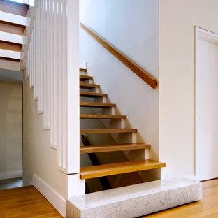 Foto de escalera minimalista, sin contrahuella, con barandilla de madera y escalones de madera