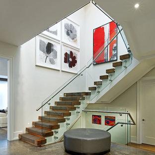 Diseño de escalera en U, actual, grande, con escalones de madera, contrahuellas de madera y barandilla de vidrio