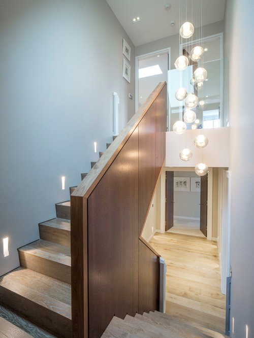 Example Of A Large Trendy Wooden Curved Staircase Design In London