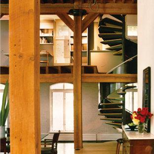 Ispirazione per una scala a chiocciola industriale con pedata in legno e nessuna alzata