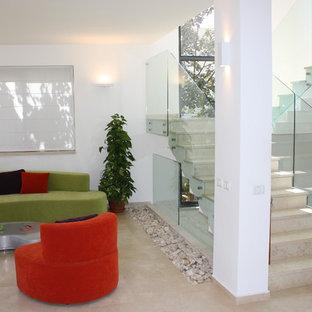 Diseño de escalera en U, moderna, con escalones de travertino, contrahuellas de travertino y barandilla de vidrio
