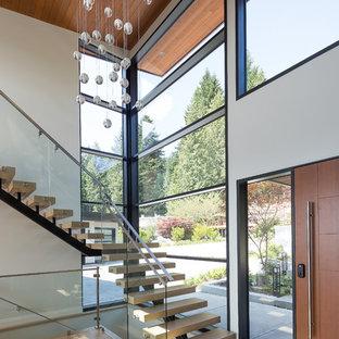 """Foto di una scala a """"L"""" minimal con alzata in vetro e parapetto in metallo"""