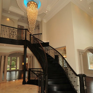 Staircase - huge traditional painted curved staircase idea in Toronto with painted risers