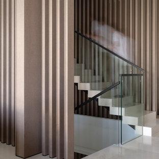 ロンドンの巨大なライムストーンのコンテンポラリースタイルのおしゃれな折り返し階段 (ライムストーンの蹴込み板、ガラスの手すり) の写真