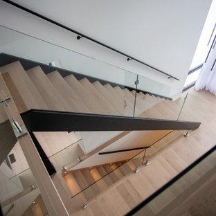 Esempio di una scala a chiocciola design con pedata in legno, alzata in legno e parapetto in vetro