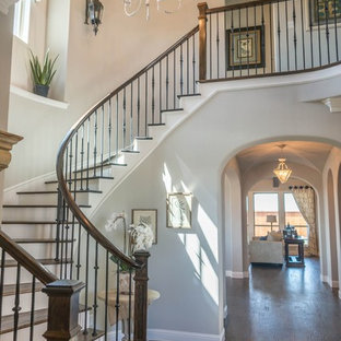 Foto de escalera curva, clásica renovada, grande, con escalones de madera, contrahuellas de madera pintada y barandilla de varios materiales