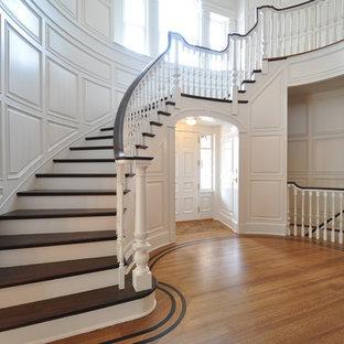Exempel på en stor klassisk svängd trappa i trä, med sättsteg i målat trä