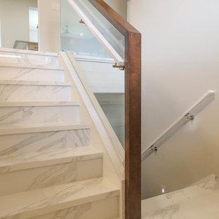他の地域の中サイズのタイルのコンテンポラリースタイルのおしゃれな折り返し階段 (タイルの蹴込み板、混合材の手すり) の写真