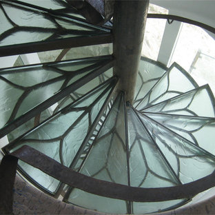 Example of a mid-sized trendy glass curved metal railing staircase design in New Orleans with glass risers