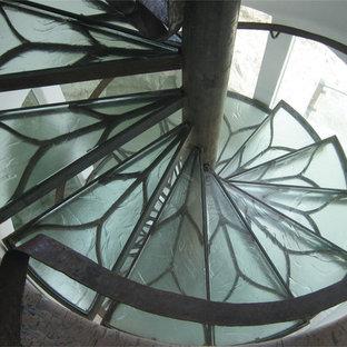 ニューオリンズの中サイズのガラスのコンテンポラリースタイルのおしゃれなサーキュラー階段 (ガラスの蹴込み板、金属の手すり) の写真