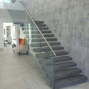 Idee per una grande scala sospesa minimal con pedata in cemento e alzata in cemento