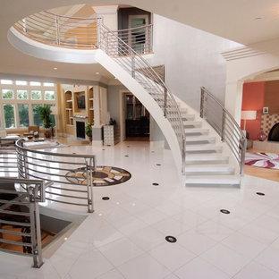 Idée de décoration pour un très grand escalier sans contremarche courbe tradition avec des marches en acrylique.