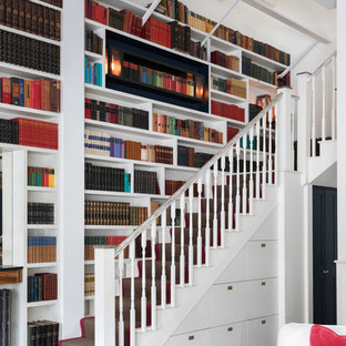 Photo of a traditional painted wood l-shaped wood railing staircase in London with painted wood risers.