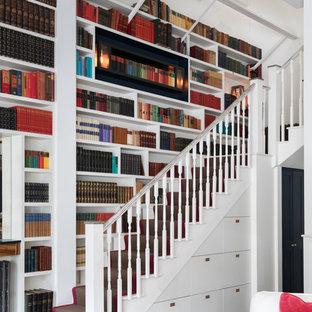 ロンドンのフローリングのトランジショナルスタイルのおしゃれなかね折れ階段 (フローリングの蹴込み板、木材の手すり) の写真