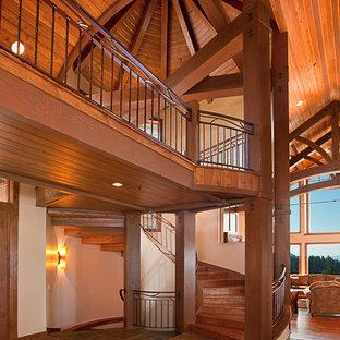Пример оригинального дизайна: большая изогнутая лестница в стиле рустика с деревянными ступенями, деревянными подступенками и металлическими перилами