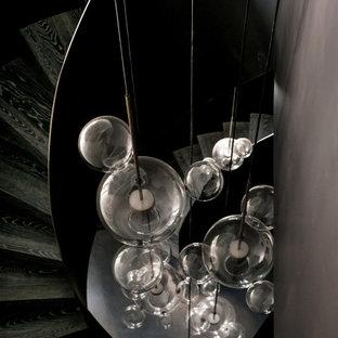 Esempio di una grande scala a chiocciola minimal con pedata in legno, alzata in metallo, parapetto in metallo e boiserie
