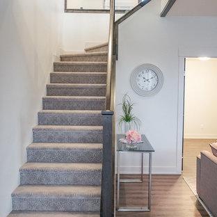 エドモントンの中くらいのカーペット敷きのシャビーシック調のおしゃれなかね折れ階段 (カーペット張りの蹴込み板、ガラスの手すり) の写真