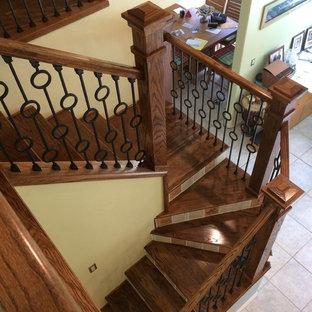 Foto de escalera en U, tradicional renovada, con escalones de madera, contrahuellas con baldosas y/o azulejos y barandilla de varios materiales