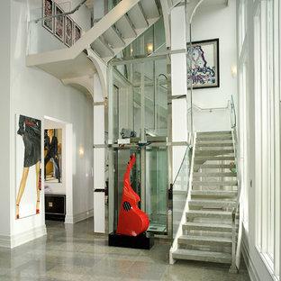 """Foto di una grande scala a """"U"""" design con nessuna alzata e pedata in marmo"""