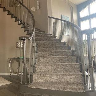 Diseño de escalera curva, tradicional renovada, grande, con escalones enmoquetados, contrahuellas enmoquetadas y barandilla de varios materiales