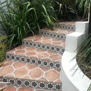 Ejemplo de escalera curva, mediterránea, con escalones de terracota y contrahuellas con baldosas y/o azulejos