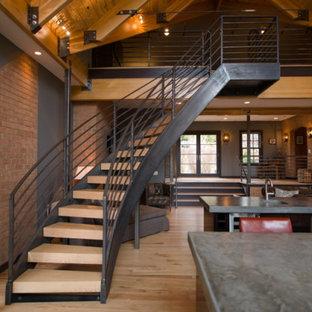 Aménagement d'un grand escalier sans contremarche courbe avec des marches en bois, un garde-corps en métal et un mur en parement de brique.