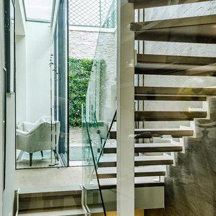 Diseño de escalera en U, actual, pequeña, con escalones de madera, contrahuellas de metal y barandilla de vidrio