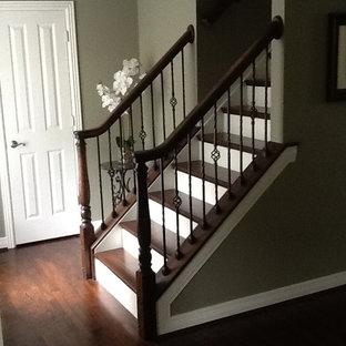 Diseño de escalera recta, clásica, de tamaño medio, con escalones de madera, contrahuellas de madera pintada y barandilla de metal