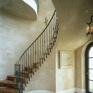 Diseño de escalera curva, mediterránea, con escalones de madera y contrahuellas de madera