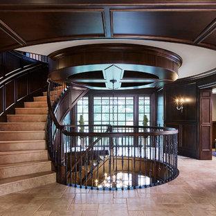 ミネアポリスの大きいライムストーンのトラディショナルスタイルのおしゃれなサーキュラー階段 (ライムストーンの蹴込み板、木材の手すり) の写真