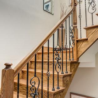 Diseño de escalera en U, tradicional renovada, de tamaño medio, con escalones de madera, contrahuellas de madera y barandilla de varios materiales