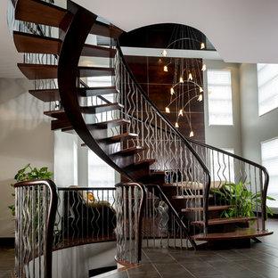 モントリオールの大きい木のトラディショナルスタイルのおしゃれなサーキュラー階段 (木の蹴込み板、金属の手すり) の写真