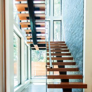 Modelo de escalera en U, urbana, grande, sin contrahuella, con escalones de madera y barandilla de vidrio