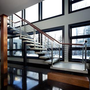 Foto de escalera suspendida, minimalista, sin contrahuella, con escalones de hormigón y barandilla de cable