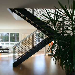 Example of a large minimalist wooden u-shaped open and metal railing staircase design in Seattle