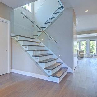 Imagen de escalera en U, contemporánea, de tamaño medio, con escalones de madera, contrahuellas de madera pintada y barandilla de vidrio