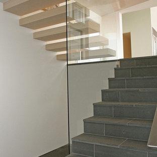 На фото: лестница в стиле модернизм с металлическими перилами, ступенями из плитки и подступенками из плитки с