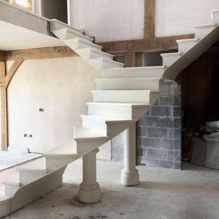 Diseño de escalera suspendida, tradicional, grande, con escalones de piedra caliza, contrahuellas de piedra caliza y barandilla de metal