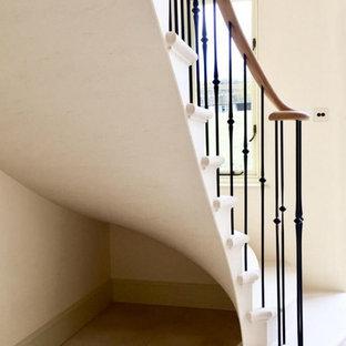 Idee per una scala curva tradizionale di medie dimensioni con pedata in pietra calcarea, alzata in pietra calcarea e parapetto in metallo