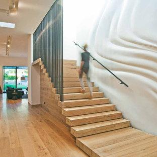 Diseño de escalera suspendida y panelado, minimalista, grande, con escalones de madera, contrahuellas de madera, barandilla de metal y panelado