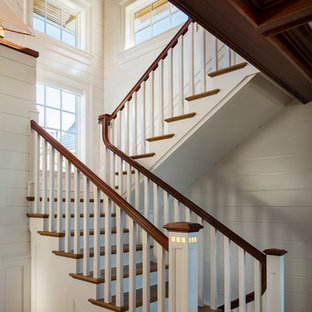 Example of a beach style wooden u-shaped wood railing staircase design in New York with painted risers