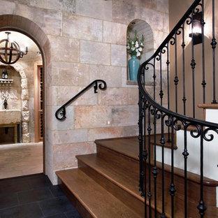 Пример оригинального дизайна: изогнутая лестница в средиземноморском стиле с деревянными ступенями, деревянными подступенками и металлическими перилами