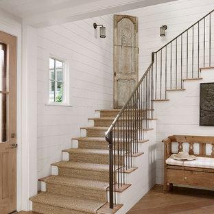 Diseño de escalera campestre con escalones de madera, contrahuellas de madera pintada y barandilla de metal