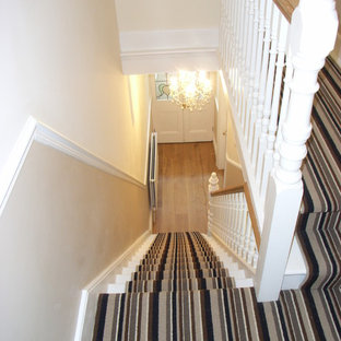 This is an example of a medium sized contemporary carpeted u-shaped staircase in Other with carpeted risers.