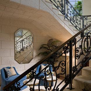 マイアミの大きいカーペット敷きの地中海スタイルのおしゃれなサーキュラー階段 (ライムストーンの蹴込み板、混合材の手すり) の写真