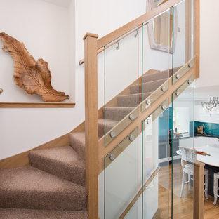 他の地域の中サイズのカーペット敷きのカントリー風おしゃれなサーキュラー階段 (ガラスの蹴込み板、木材の手すり) の写真
