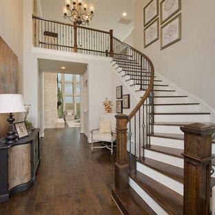 Diseño de escalera curva, clásica, con escalones de madera y contrahuellas de madera pintada