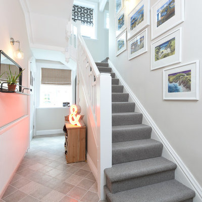 Inspiration for a transitional carpeted u-shaped wood railing staircase remodel in Manchester with carpeted risers