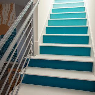 他の地域の中サイズのフローリングのミッドセンチュリースタイルのおしゃれな直階段 (フローリングの蹴込み板、金属の手すり) の写真
