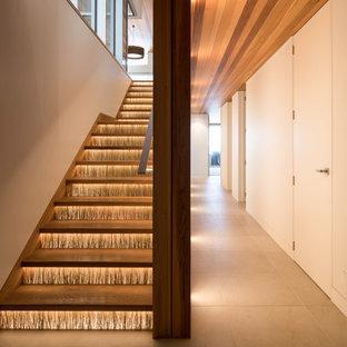 Ejemplo de escalera en L, costera, pequeña, con escalones de madera, contrahuellas de vidrio y barandilla de madera